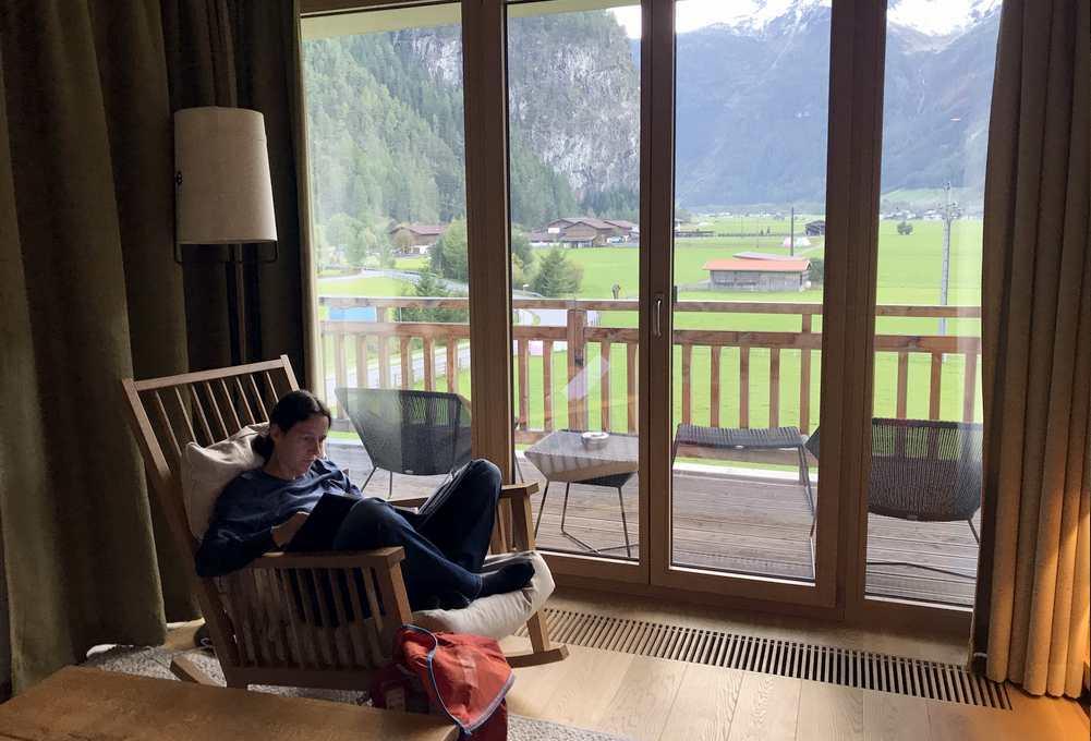 Das gemütliche Wohnzimmer mit Schaukelstuhl und Ausblick auf die Alpen