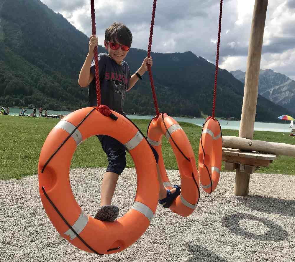 Im Niederseilgarten am Atoll-Spielplatz am Achensee müssen die Kinder über die Rettungsringe klettern