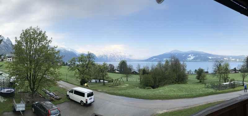 Am nächsten Morgen: Der Blick von der Ferienwohnung über den Attersee mit blauem Himmel und Schnee auf den Bergen
