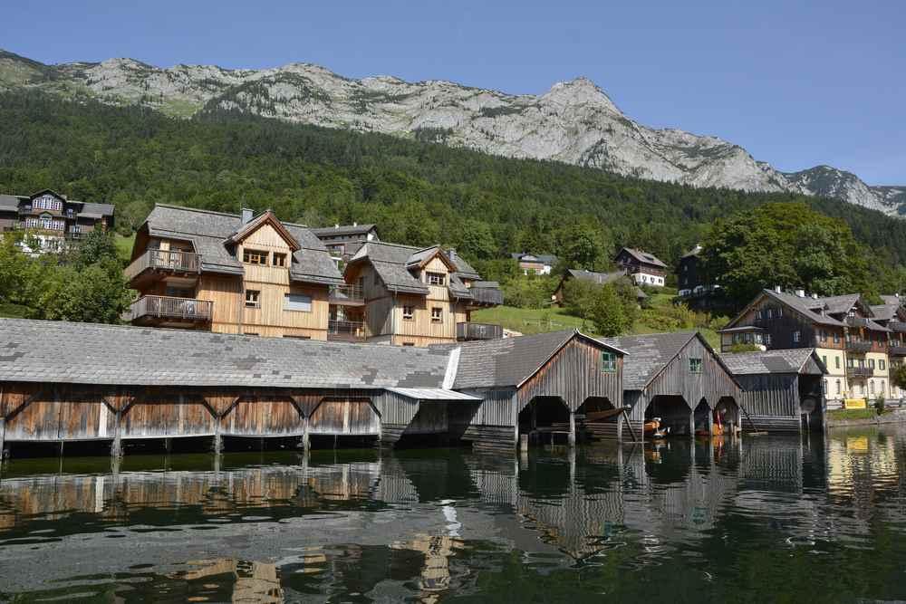 Vorne stehen die rustikalen Bootshäuser am Grundlsee, dahinter die Wohnhäuser, zu sehen auf der Drei Seen Tour