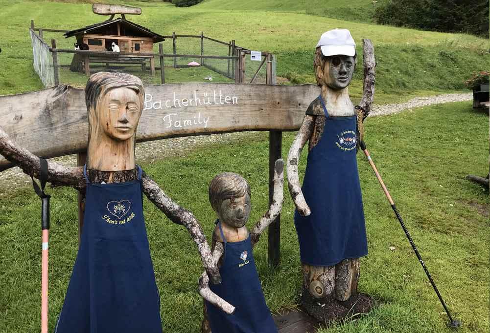 Vor der Bacherhütte steht die Familie aus Holz und begrüßt die Wanderer