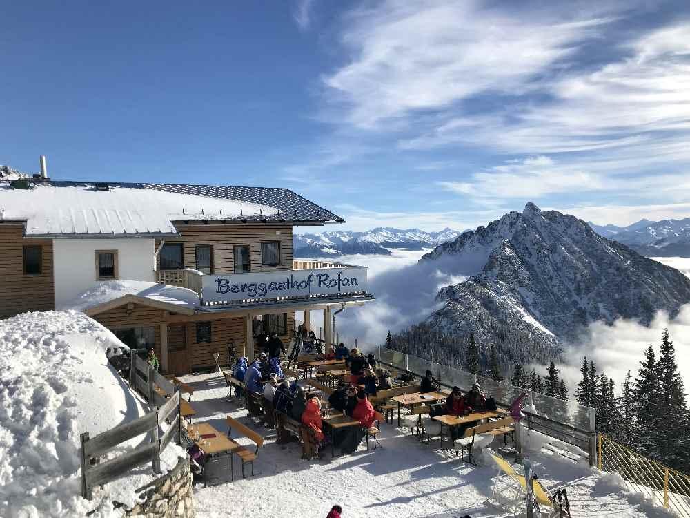 Das ist die Sonnenterrase beim Berggasthof Rofan mit dem verschneiten Rofangipfel