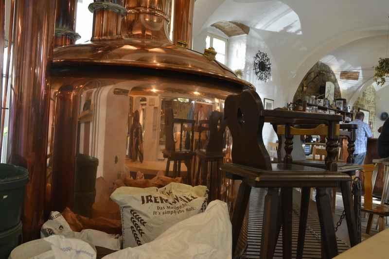 Griesbräu Murnau:  Neben den Braukesseln stehen die Stühle zum Sitzen und Bier trinken