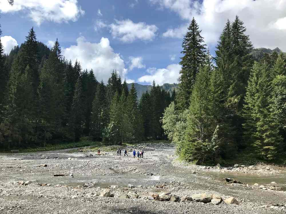 Der Bach im Derratal ist breit, rechts vom Ufer verläuft unser Wandersteig hinauf