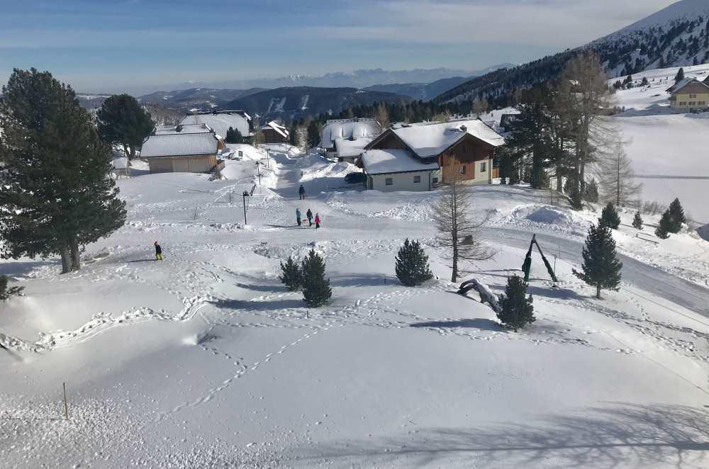 Vom Familienhotel geht es durch die verschneite Siedlung in Falkertsee zur Rodelbahn