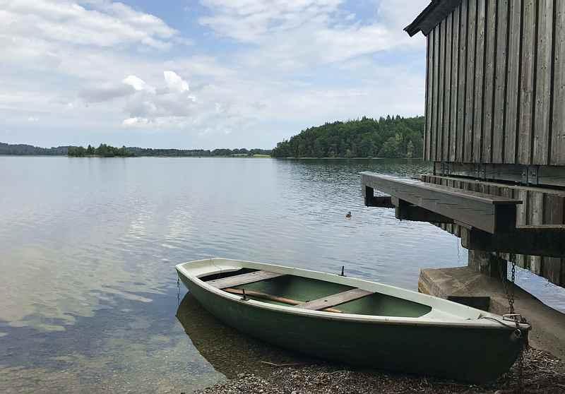 Staffelsee Radweg: Direkt am Ufer des Staffelsees fahren wir mit dem Fahrrad entlang. Unterwegs gibt es Hütten und auch Ruderboote zu sehen.