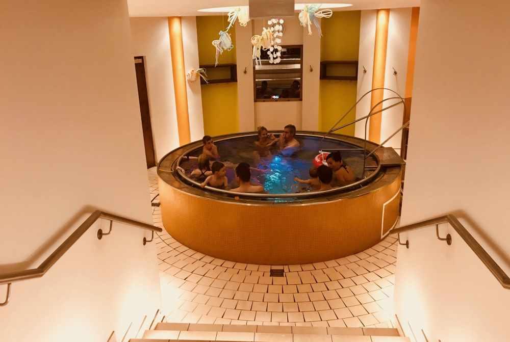 Familienhotel Bad Kleinkirchheim:  Vom großen Schwimmbecken geht es hinunter zum stimmungsvollen Familienbad und der Familiensauna