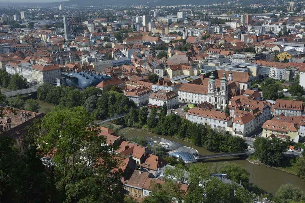 Auf dem Weg vom Glockenturm zum Uhrturm haben wir diese schöne Aussicht über Graz. Schön zu sehen: Rechts in der Mur die Murinsel und links oberhalb das Kunstmuseum mit der eigentümlichen Gebäudeform.