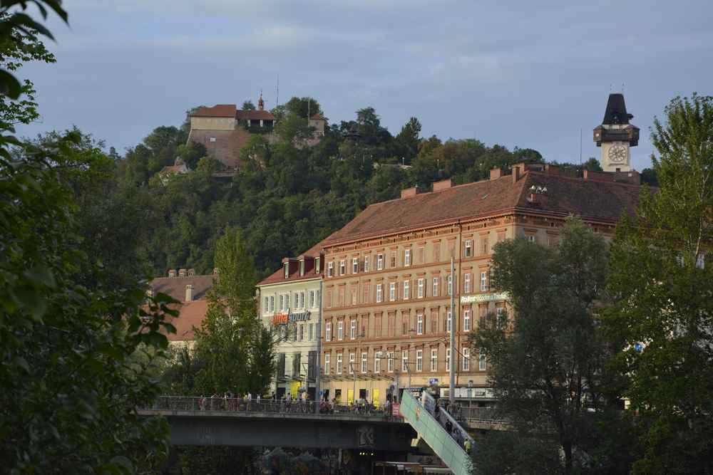 Unser Start in den Familienurlaub Graz - wir stehen an der Mur und schauen hinauf zum Schlossberg