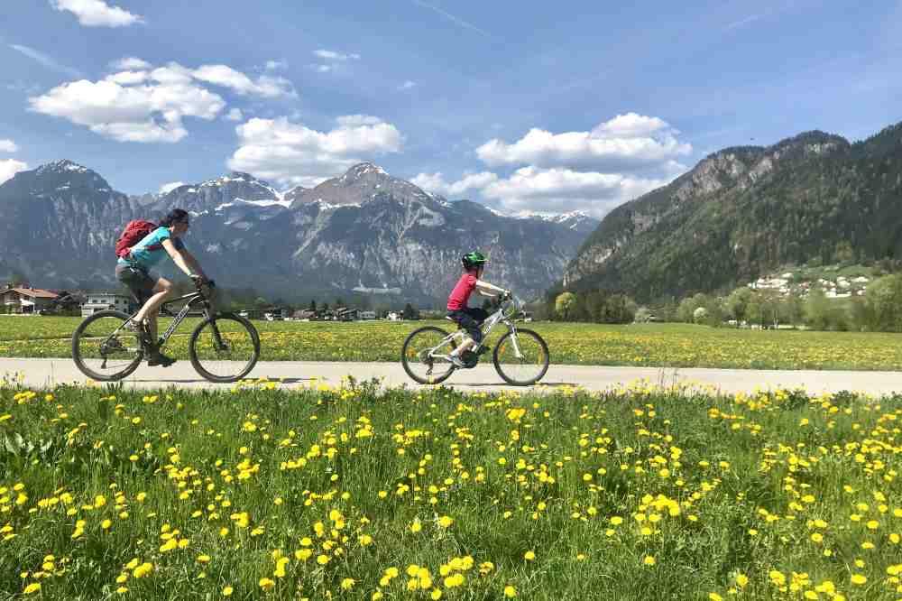 Radreisen mit Kindern sind im Frühling besonders schön: Durch die grünen Wiesen und zwischen dem frischen Grün auf die Berge schauen