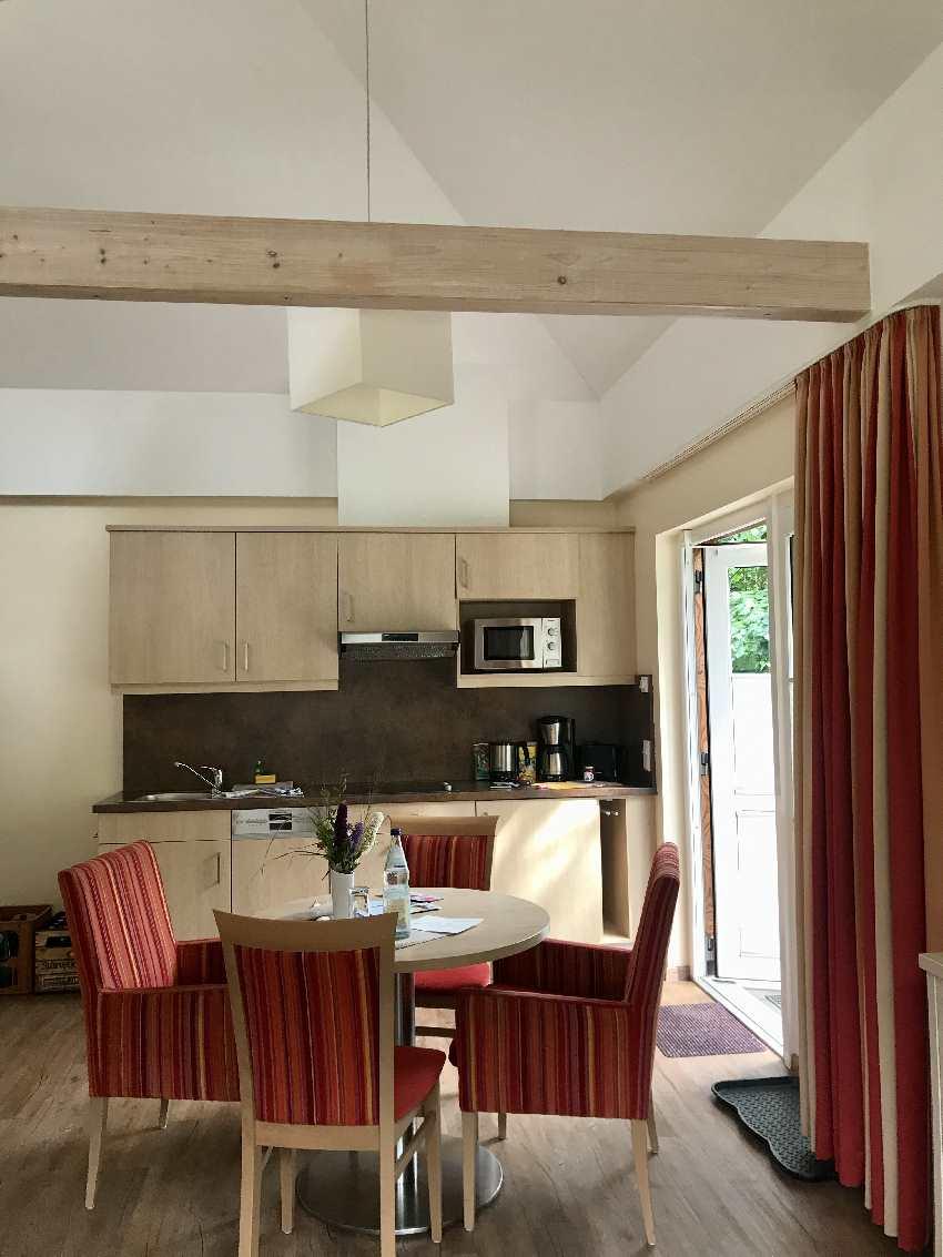 Das Wohnzimmer mit Tisch und Küche