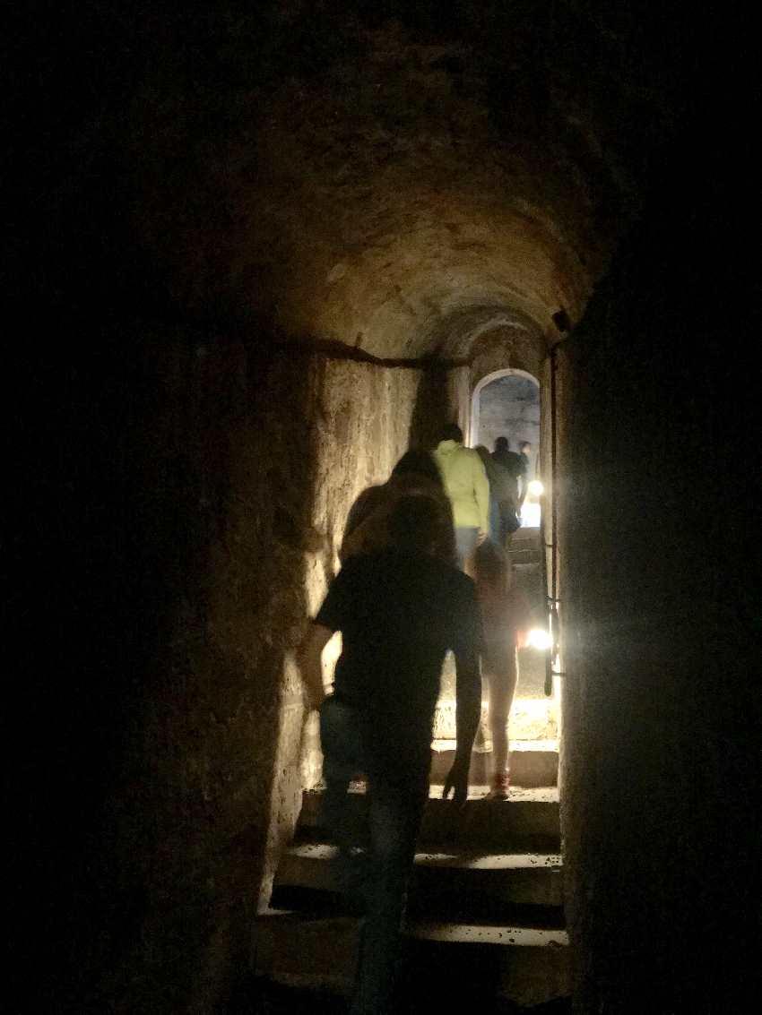 Durch den Felsengang kommen wir unter der Burgmauer hindurch