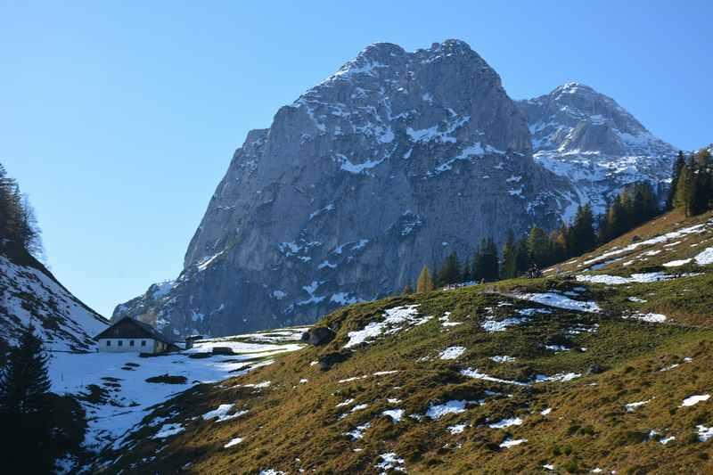 Halsalm wandern: Links im Schatten die Alm in den bayerischen Alpen