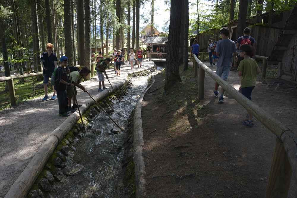 Im Holzknechtland können Kinder mit den langen Holzstecken das Holz auf der Bürgeralpe triften