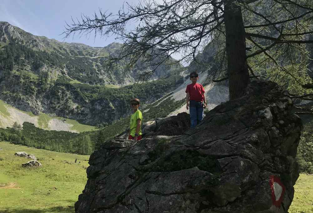 Bei der Holzeralm liegt ein hausgroßer Stein - den die Kinder zu einer Klettereinlage nutzen