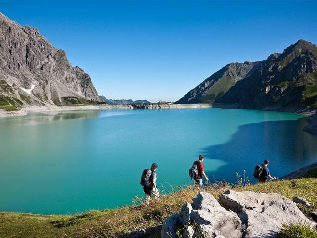 Der türkisgrüne Speichersee Lünersee in Vorarlberg. Wanderweg rund um den See. Bild: Brandnertal Tourismus