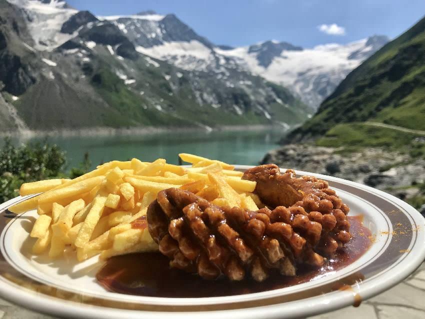 Im Mooserboden Restaurant holen wir uns eine Currywurst - gegessen wird mit diesem Seeblick!