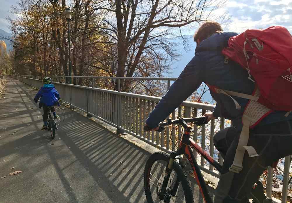 Wir fahren am späten Vormittag mit dem Fahrrad am Ufer des Millstätter See der Sonne entgegen