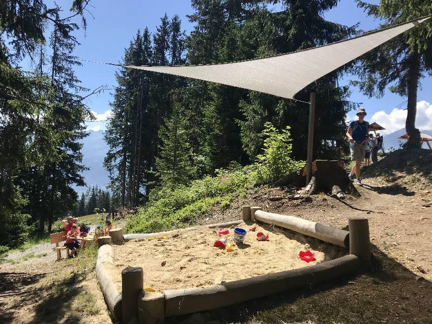 Durchdachtes Abenteuer am Berg mit Kindern - sogar ein Sandspielplatz mit Sonnensegel neben der Pausenbank