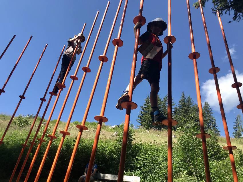 Auf zwei Ebenen klettern die Kinder von Stange zu Stange