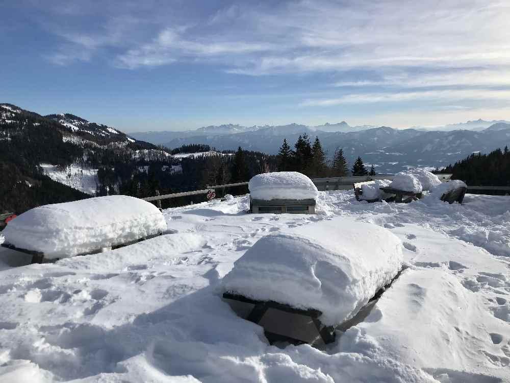 Die Bänke im Freien sind tief verschneit.