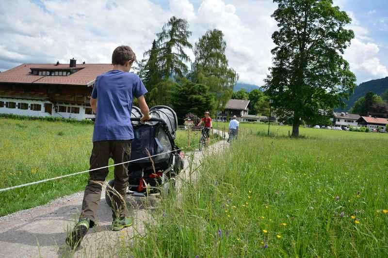 Auf einem Weg zwischen den Wiesen wandern wir mit dem Kinderwagen nach Abwinkl
