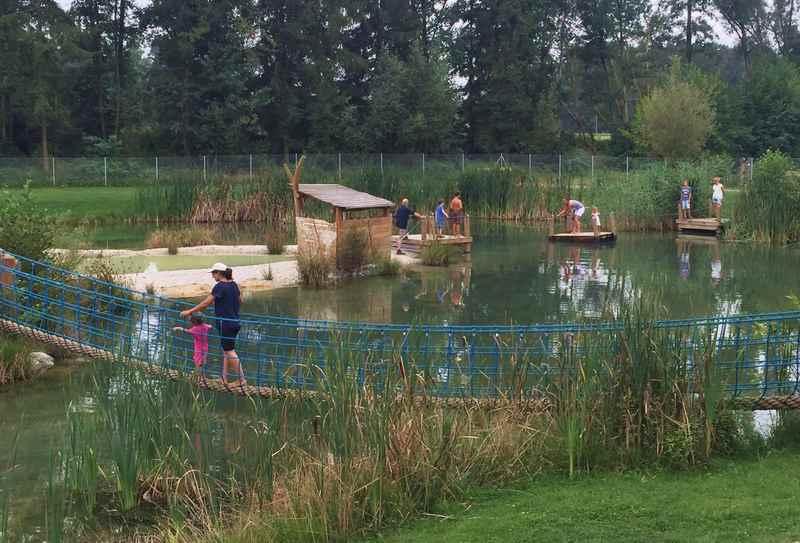 Murner See Spielplatz mit Floß und Hängebrücke über dem Wasser