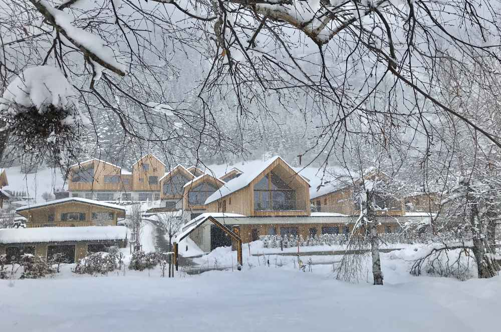 Von den Holzhütten und Chalets des Regitnig wandern wir durch den Schnee zur Rodelbahn in Weissensee