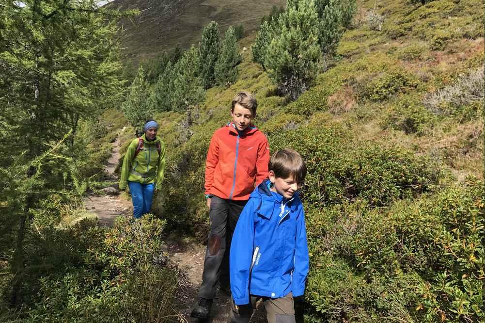 Meransen Wandern mit Kindern: In der Sonne auf dem Weg zur Bergbahn, für die Fahrt ins Tal nach Meransen
