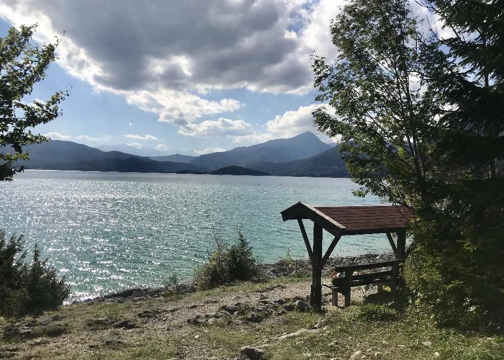 Walchensee Radweg: Oberhalb der Felsen sitzen wir auf der Aussichtsbank und schauen über das Wasser und auf die Berge