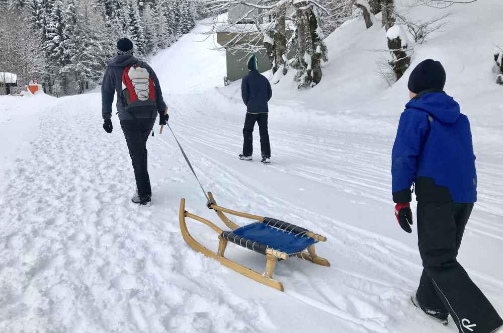 Weissensee rodeln - Wir lassen uns vom Neuschnee nicht abhalten und spuren auf der Rodelbahn hinauf unseren Weg