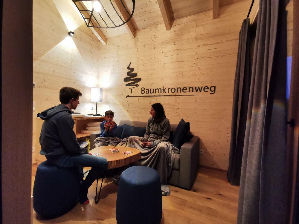 Das Wohnzimmer mit Tisch und hoher Holzdecke - sehr gemütlich und ideal zum Spielen