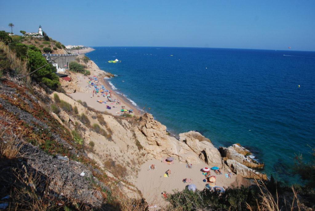 Calella Spanien - rechts der Strand, links auf der Anhöhe der Leuchtturm