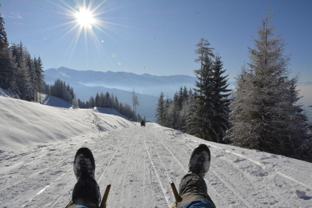 Eine Rodelbahn Tirol geniessen - mit einer kilometerlangen Abfahrt der Sonne entgegen