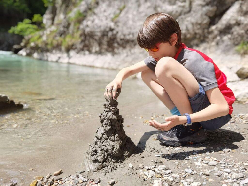 Matschtürme bauen am Ufer der Kössen Klamm