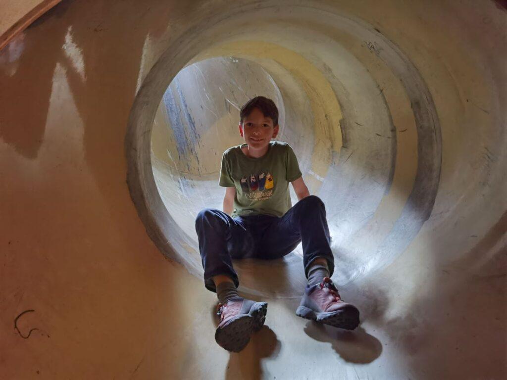 Wir probieren die Rutsche aus und kommen in einem Tunnel heraus
