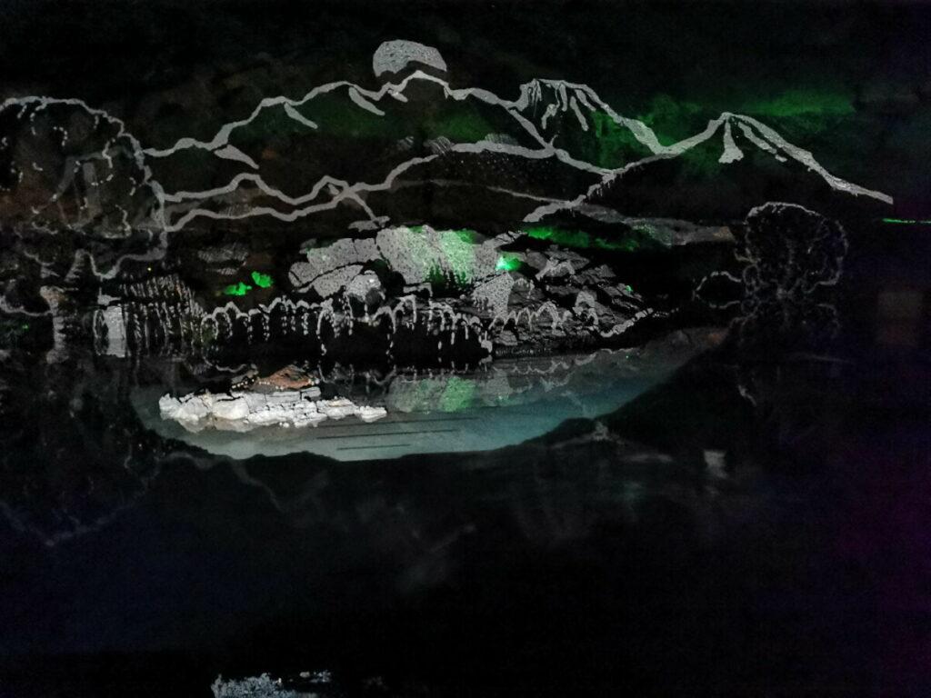 Lichtershow in den Salzwelten Hallstatt - die Figuren spiegeln sich im Salzsee
