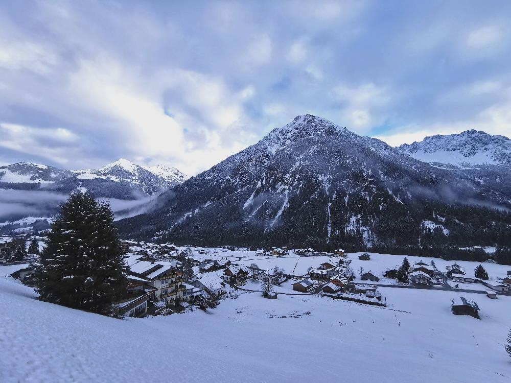 Links im Bild das Hotel Rosenhof Kleinwalsertal, dahinter die Winterlandschaft mit den Bergen