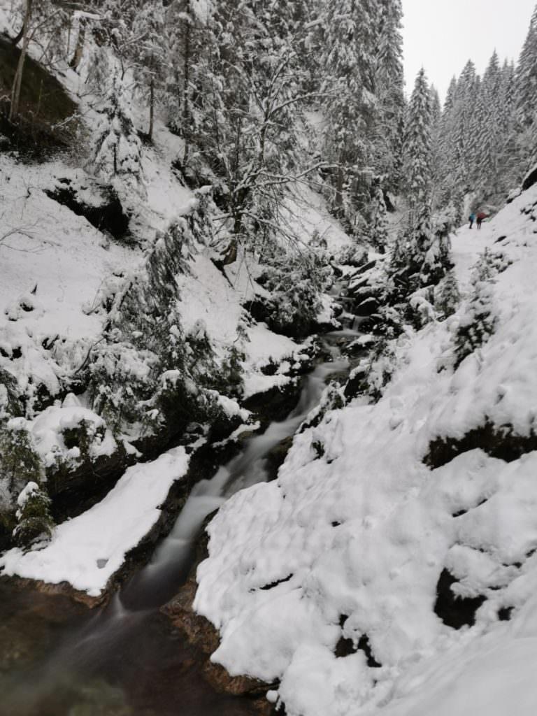 Winterwandern Kleinwalsertal Bergunt - Wasserfall und rechts klein die Leute am Wanderweg