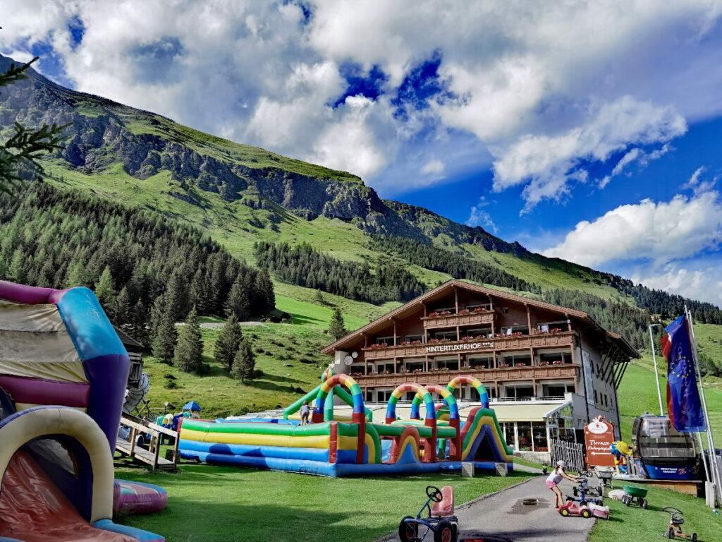 Familienhotel Hintertuxerhof - traumhaft gelegen umgeben von Bergen, mit großem Spielplatz neben der Sonnenterrasse