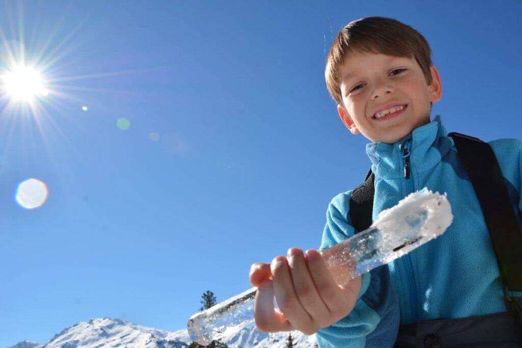 Rodeln mit Kindern - dazu gehört auch das Spielen im Schnee, samt der Suche nach großen Eiszapfen...